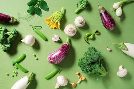 Fresh raw organic vegetables on the textured green table, concept of healthy eating and organic gardening, top view