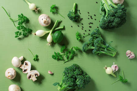 Fresh organic vegetables on the green table, raw ingredients for cooking, concept of healthy eating, top view