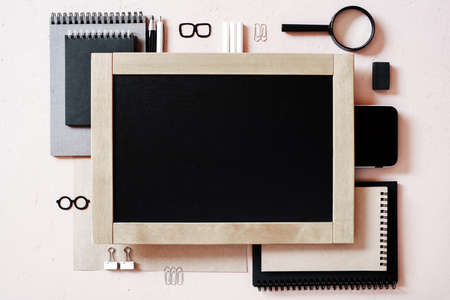 Education supplies and chalkboard on the textured beige table, overhead view