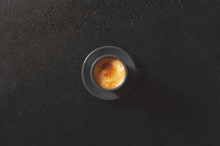 The cup of espresso coffee on black table, overhead view Stockfoto