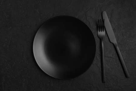 Black background with plate and cutlery, monochrome table setting Stockfoto