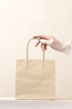 Concept of safe delivery in the period of pandemic. Gloved hand holding the paper bag.