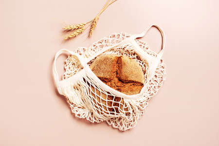 Organic rye bread in the mesh bag on beige table, top view