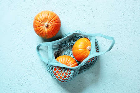 Three pumpkins in the mesh bag on the blue textured table, top view Stockfoto