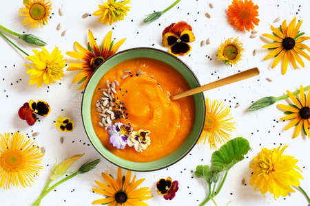 Pumpkin cream soup decorated with autumn flowers on the textured white table, top view