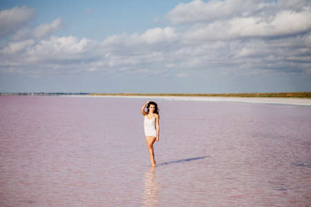 Beautiful girl on a pink lake.
