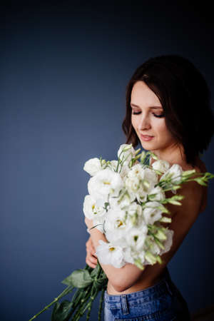 Beautiful girl with a bouquet flowers.