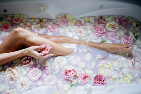 Beautiful girl in the bathroom with many flowers.