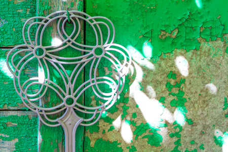 A carpet beater hangs from a cracked wall with a nail. Cracks in the paint. From time to time, the coating fell into disrepair.
