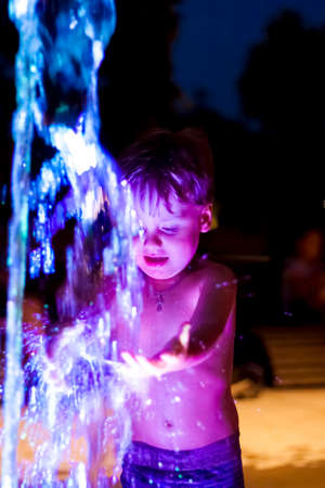 The child is frolicking in the fountain in the park, he is very happy. Have fun and enjoy the summer evening. Walking and recreation. Portrait of a happy child. Night shooting Standard-Bild