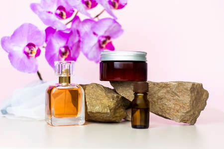 A cosmetic product and a perfume bottle stand on a stone against a background of beautiful orchids. Stylish appearance, layout, personality. Banner, a place for the text. The concept of cosmetics for care.