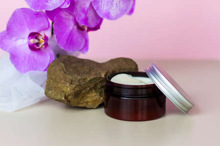 A brown jar of cream on a pink background stands on a large building stone with beautiful orchids next to it. Stylish appearance of the product, layout, personality. Banner, a place for the text.