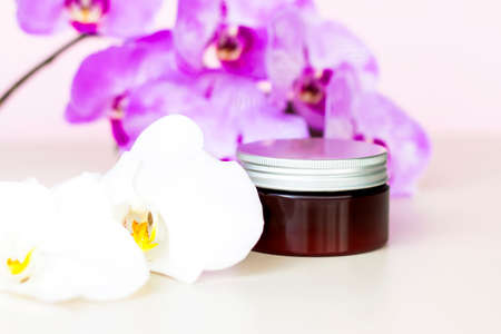 A brown jar of cream on a pink background with beautiful orchids. Stylish appearance of the product, layout, personality. Banner, a place for the text.