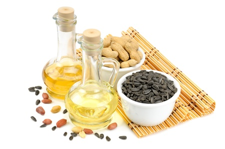 Sunflower seeds, peanuts and bottle of oil isolated on a white background                                     Stock Photo