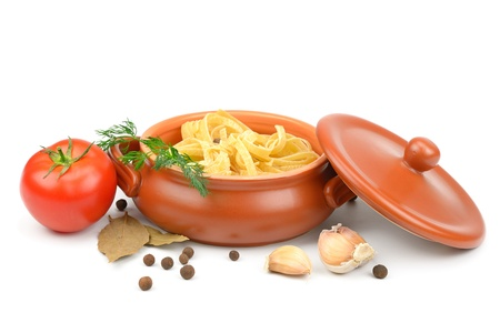 Clay pot with pasta, vegetables and spices isolated on white background.