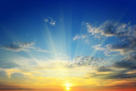 die Sonnenstrahlen beleuchten den Himmel über dem Horizont Standard-Bild