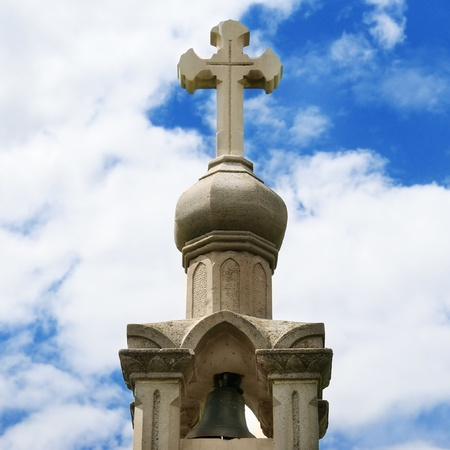 Stone cross on blue sky background                                     photo