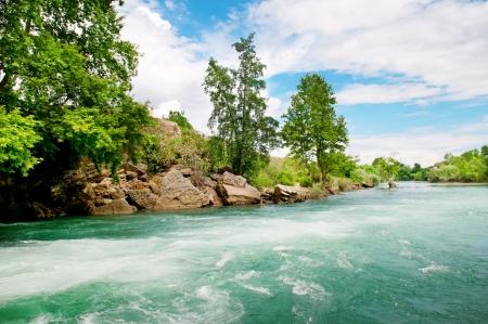 岩石の多い海岸の川と青い空 写真素材