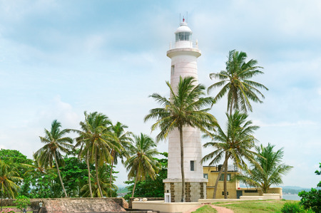 Lighthouse and palm trees in the town of Galle, Sri Lanka photo