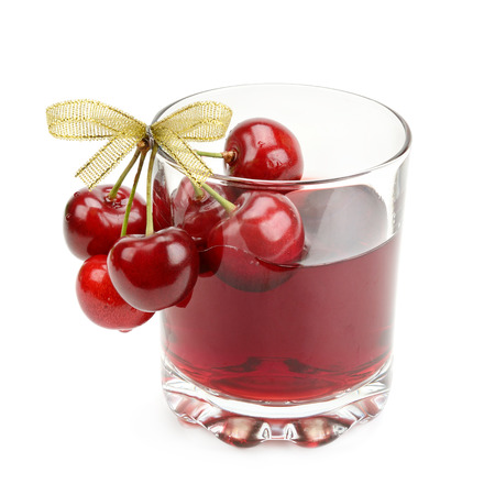 cherry and glass of juice isolated on white background photo