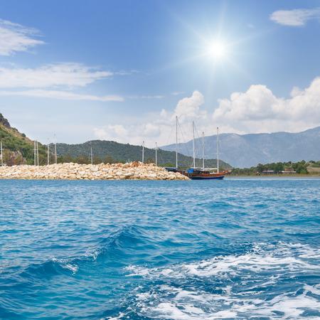 scenic seascape, blue sky, sun, yacht photo