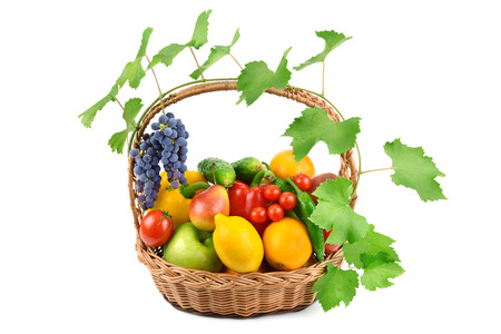 fruits and vegetables in a wicker basket isolated on white background photo