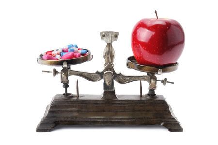 bowls of scales, apple and pills isolated on white background photo