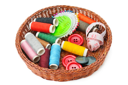 thread and buttons in a basket isolated on white background photo