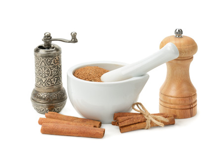 cannelle: cinnamon, mortar and pestle, hand grinder isolated on white