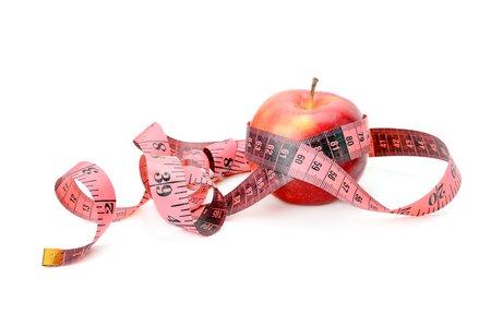 losing control: apple and measuring tape isolated on white background