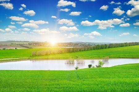 uprise: green field, lake and sunrise