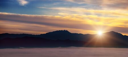 Bright sunrise, the mist in a mountain valley and mountain peaks on the horizon.