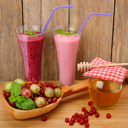 berry smoothie, currants, gooseberries and honey on a wooden surface Stock Photo