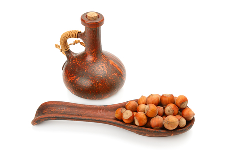 hazelnuts and oil from nuts in clay bottle isolated on white background