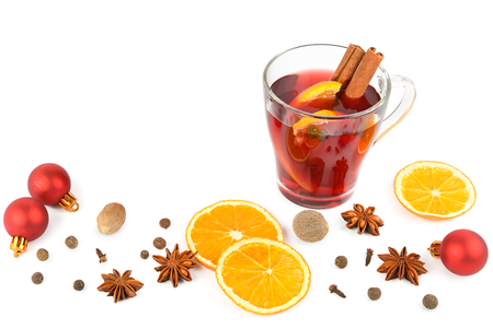 Hot red mulled wine isolated on white background with christmas spices, orange slice, anise and cinnamon sticks, close up. Flat lay, top view. Free space for text.