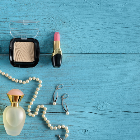 Cosmetics, perfumes and jewelry made of pearls on an old wooden background of blue color