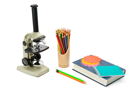 Laboratory microscope, textbook and other school supplies isolated on white background. Free space for text. Stock Photo