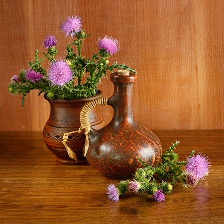 Oil and flowers of milk thistle on wooden background.