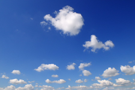 Light cumulus clouds against the blue sky. A bright sunny day.