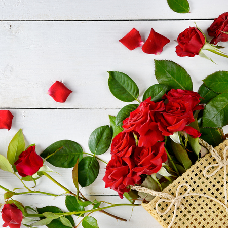 Flowers composition. Red roses on a white wooden background. Free space for text. Flat lay, top view.