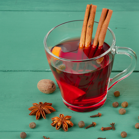 Hot red mulled wine on wooden background with spices, orange slice, anise and cinnamon sticks, close up.