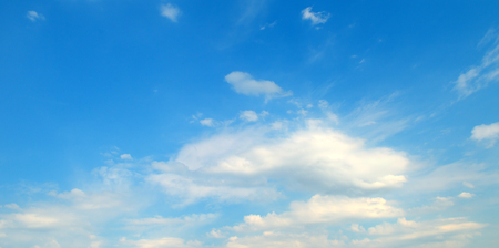 Light cumulus clouds against the blue sky. A bright sunny day. Wide photo. Stock Photo