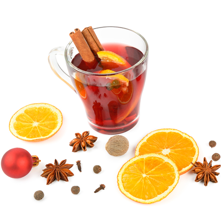 Hot red mulled wine isolated on white background with spices, orange slice, anise and cinnamon sticks, close up. Flat lay, top view.