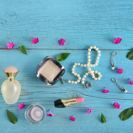 Cosmetics, perfumes and jewelry made of pearls on an old wooden background of blue color. Flat lay, top view. Free space for text. Stock Photo