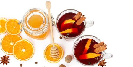 Hot red mulled wine, bee honey, slices of oranges and spices isolated on white background. Flat lay, top view. Free space for text. Wide photo.