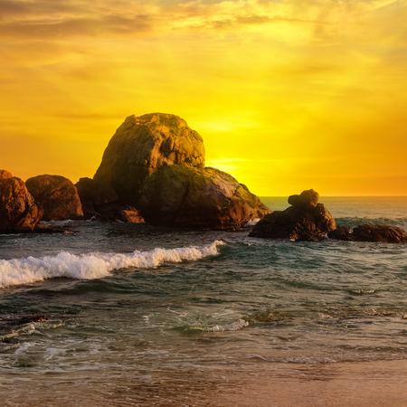 Sea landscape with rocky island and the sunrise. Beach. Sri Lanka.