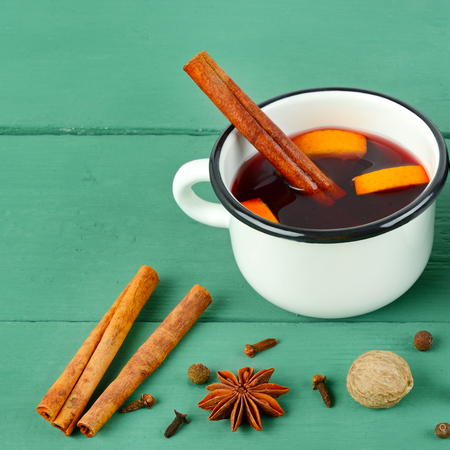 Hot red mulled wine on wooden background with spices, orange slice, anise and cinnamon sticks, close up. Free space for text.