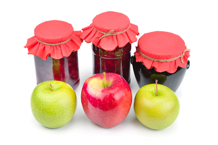 Apple jam in a glass jar, fresh red and green apples isolated on white background. Healthy food