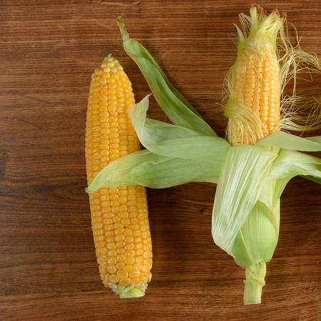Fresh corn cob on wooden table. Healthy food.
