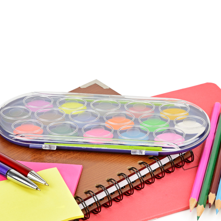Watercolor paints, notebooks and other school supplies isolated on white